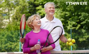 an older couple standing together taking a break from their tennis match