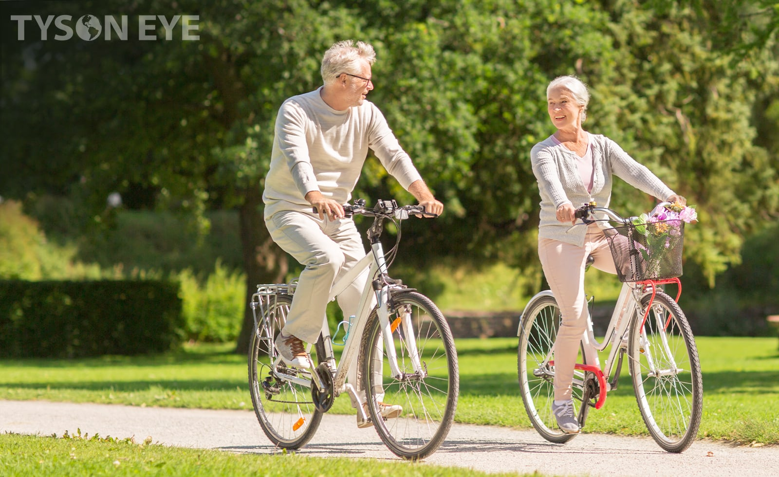 An elderly couple riding bicycles in a park